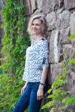 Belle jeune femme se tenant près d'un mur en pierre Photos stock