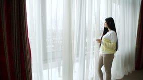 Belle jeune femme se tenant regardante la fenêtre banque de vidéos