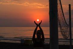 Belle jeune femme se tenant sur la plage, tenant le soleil dans des mains Images stock
