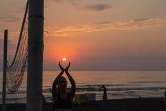 Belle jeune femme se tenant sur la plage, tenant le soleil dans des mains Photo stock