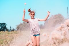 Belle jeune femme se trouvant sur le champ en herbe verte et pissenlit de soufflement outdoors Appréciez la nature Fille de souri image stock