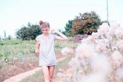 Belle jeune femme se trouvant sur le champ en herbe verte et pissenlit de soufflement outdoors Appréciez la nature Fille de souri photographie stock libre de droits