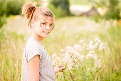 Belle jeune femme se trouvant sur le champ en herbe verte et pissenlit de soufflement outdoors Appréciez la nature Fille de souri images libres de droits