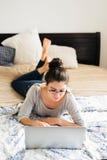 Belle jeune femme se trouvant sur le lit, fonctionnant Siège social Photographie stock libre de droits