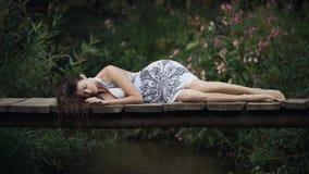 Belle jeune femme se trouvant sur le pont au-dessus de la rivière de forêt photos stock