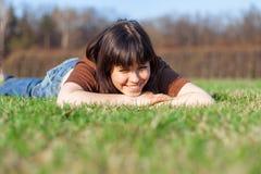 Belle jeune femme se trouvant sur un champ, herbe verte Appréciez dehors la nature image stock