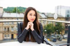 Belle jeune femme seul s'asseyant en café sur une attente de terrasse l'ordre Pause-café après l'achat Belle jeune femme ayant Image libre de droits