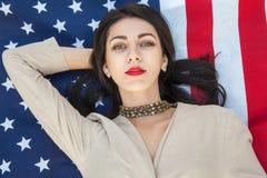 Belle jeune femme sexy avec la robe classique se couchant sur le drapeau américain en parc mannequin tenant le sourire et le look Photographie stock libre de droits