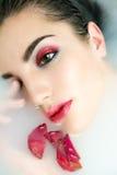 Belle jeune femme avec les cheveux foncés humides et maquillage en lait Photo stock