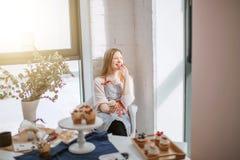 Belle jeune femme souriant et ayant le cupcak photographie stock libre de droits