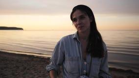 Belle jeune femme souriant et parlant au coucher du soleil près de la mer banque de vidéos