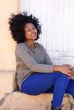 Belle jeune femme souriant et s'asseyant sur des étapes en dehors de porte Photo stock