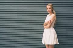 Belle jeune femme souriant et se tenant avec les bras croisés contre le mur gris photographie stock