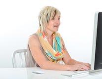 Belle jeune femme supérieure travaillant au bureau avec l'ordinateur Images stock