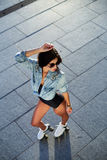Belle jeune femme sur des patins de rouleau et un casque rose photo stock
