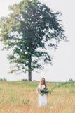 Belle jeune femme sur le fond d'un grand arbre avec un bouquet des fleurs dans leurs mains Photo libre de droits
