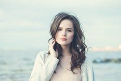 Belle jeune femme sur le fond naturel bleu Image stock
