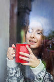 Belle jeune femme sur un balcon derrière le verre Image stock