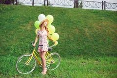 Belle jeune femme sur une bicyclette sur un fond vert de pelouse Photographie stock