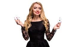 Belle jeune femme tenant l'as deux des cartes dans sa main d'isolement sur le fond noir Image stock