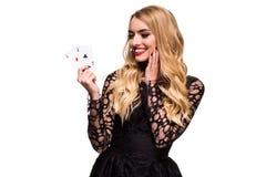 Belle jeune femme tenant l'as deux des cartes dans sa main d'isolement sur le fond noir Image libre de droits