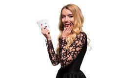 Belle jeune femme tenant l'as deux des cartes dans sa main d'isolement sur le fond noir Images libres de droits