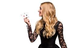 Belle jeune femme tenant l'as deux des cartes dans sa main d'isolement sur le fond noir Photo stock