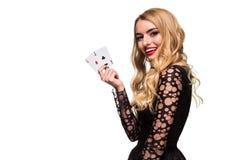 Belle jeune femme tenant l'as deux des cartes dans sa main d'isolement sur le fond noir Photos stock