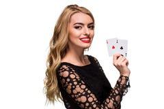 Belle jeune femme tenant l'as deux des cartes dans sa main d'isolement sur le fond noir Images stock