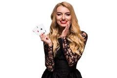 Belle jeune femme tenant l'as deux des cartes dans sa main d'isolement sur le fond noir Photographie stock libre de droits