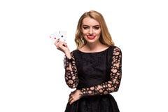 Belle jeune femme tenant l'as deux des cartes dans sa main d'isolement sur le fond noir Photographie stock