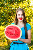 Belle jeune femme tenant la moitié d'une pastèque juteuse Image stock