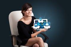 Jeune femme tenant le comprimé avec les dispositifs modernes en nuages photos stock
