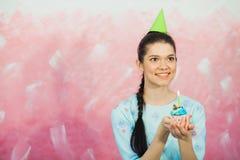 Belle jeune femme tenant le petit gâteau d'anniversaire et faisant le souhait Images libres de droits