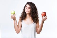 Belle jeune femme tenant les pommes vertes et rouges au-dessus du fond blanc Images stock