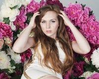 Belle jeune femme tenant sa tête sur un fond des fleurs Photographie stock libre de droits