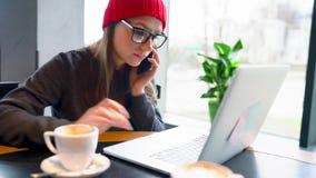 Belle jeune femme travaillant et parlant d'un smartphone dans un café banque de vidéos