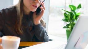 Belle jeune femme travaillant et parlant d'un smartphone dans un café clips vidéos