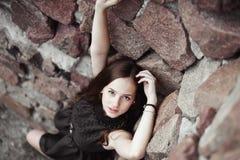 Belle jeune femme triste sur un fond de mur en pierre Image stock