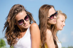 Belle jeune femme trois dans des lunettes de soleil au-dessus de ciel bleu Photographie stock