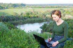 Belle jeune fille à l'aide de son comprimé graphique se reposant dans l'herbe Images libres de droits
