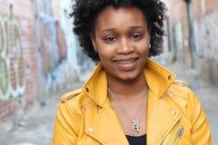 Belle jeune fille africaine souriant dans une allée photos stock