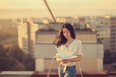 Belle jeune fille au toit avec la grue de papier d'origami dans des mains image libre de droits