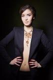 Belle jeune fille avec de beaux bijoux chers élégants, collier, boucles d'oreille, bracelet, anneau, filmant dans le studio Image libre de droits