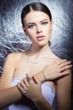 Belle jeune fille avec de beaux bijoux chers élégants, collier, boucles d'oreille, bracelet, anneau, filmant dans le studio Photographie stock libre de droits