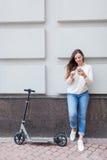 Belle jeune fille avec de longs cheveux bruns arrêtés tout en montant le scooter, pour écrire à un ami au téléphone sur le fond d Photos libres de droits