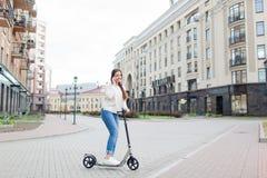 Belle jeune fille avec de longs cheveux bruns arrêtés tout en montant le scooter pour parler à un ami au téléphone sur le fond de Photographie stock libre de droits