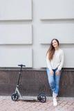 Belle jeune fille avec de longs cheveux bruns arrêtés tout en montant le scooter sur le fond du mur gris Elle est habillée dans a Photos stock