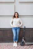Belle jeune fille avec de longs cheveux bruns arrêtés tout en montant le scooter sur le fond du mur gris Elle est habillée dans a Image libre de droits