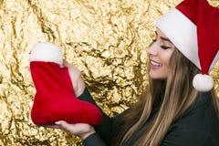 Belle jeune fille avec de longs cheveux dans un chapeau de Santa Claus avec du Re Photo stock